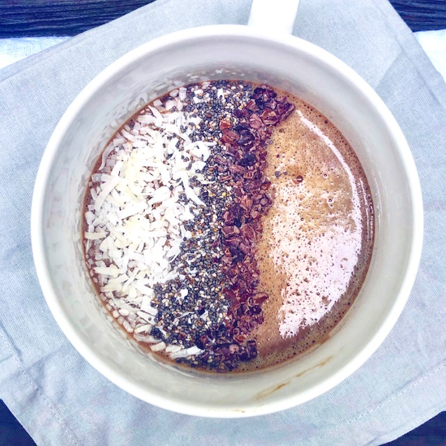 Cafe latte protein smoothie in a mug topped with chia cacao nibs and coconut